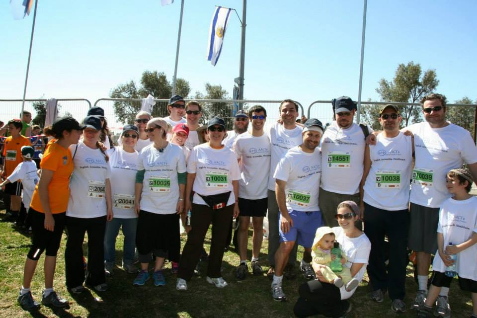 Some of the 2014 Jerusalem Marathon team takes a brief break from stretching to pose for a picture